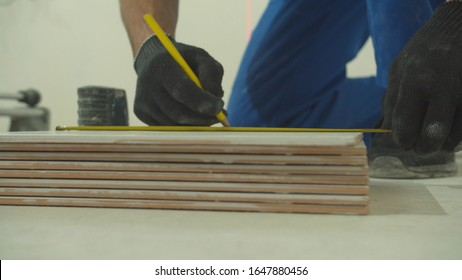 Close up, man measures a length of a tile