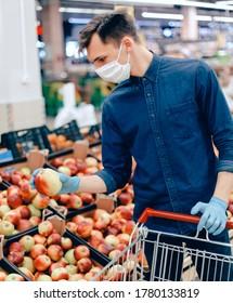 cerrar. hombre con una máscara protectora al seleccionar manzanas en el supermercado.