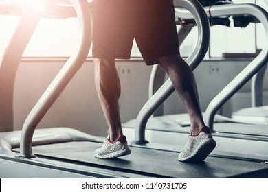 Close up. Man in Sneakers on Treadmill in Gym. Man with Athletic Body. Healthy Lifestyle and Sport Concepts. Young Man in Training Club. Active Indoor Training. Sport Equipment in Studio.