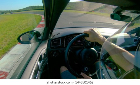 CLOSE UP: Man wearing a helmet races his fast car along the fun racetrack. Unrecognizable adrenaline seeking male race car driver having fun by driving his awesome sportscar along a closed track.