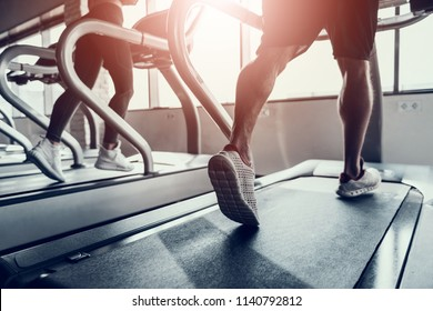 Close up. Man and Young Woman on Treadmills in Gym. Man with Athletic Body. Healthy Lifestyle and Sport Concepts. Young Woman in Training Club. Active Indoor Training. Sport Equipment.