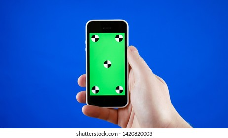 Close up. A man's hand holds a smartphone with a green screen. Blue screen background and the tracking markers.