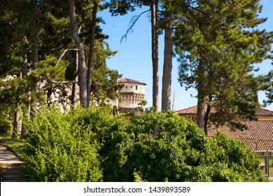 Close up. Medieval castle (Castello di Brescia) with a tower and drawbridge in Brescia, Lombardy, Italy. Italian architecture. Roman ancient castle. A view through the trees.