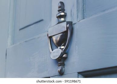 Close up, metal classic exterior house door knocker, on a pastel blue painted door, UK, England.