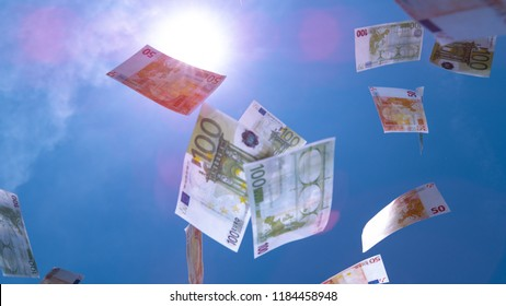 CLOSE UP: € Money falling from the sky. Fifty and hundred euro bills falling from blue skies. Successful business bringing piles of money. Profitable job and big salary. Winning lottery