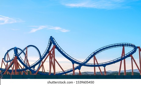 CLOSE UP: Panoramic view of an empty rollercoaster ride with sharp turns and twists on a sunny summer evening in LA, California. Cool view of a breathtaking funfair ride on the Santa Monica Pier.