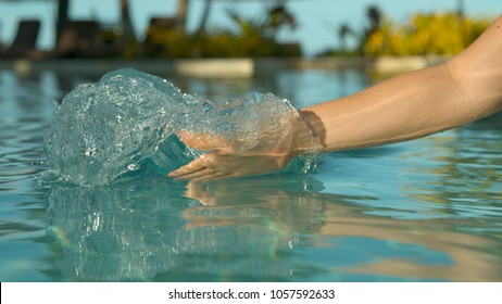CLOSE UP: Playful female tourist drags her hand through pool water and creates a cool wave. Unrecognizable Caucasian woman on summer vacation plays in crystal clear pool in sunny oceanfront resort.
