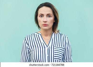 Close up, portrait bad mood business woman. Unhappy business woman looking at camera with tired face. Isolated on light blue background