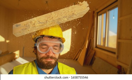 CLOSE UP, PORTRAIT: Wooden board falls on a young worker's head. Small plank falls from above on an unsuspecting contractor's head. Protective hard hat saves Caucasian builder's from a concussion.