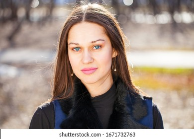 Close up, Portrait of a young beautiful woman in blue coat in spring park