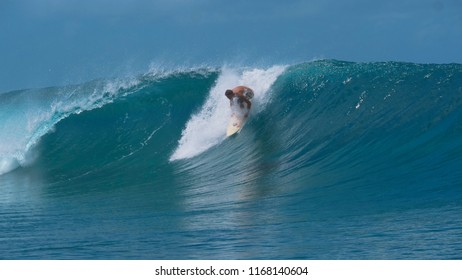 CLOSE UP: Pro male surfer stands up on his surfboard and catches a big emerald wave forming near a popular surf spot in sunny Tahiti. Young sportsman on active summer holiday having fun surfing.