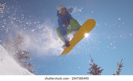 CLOSE UP: Professional snowboarder does a spectacular mid-air grab during his downhill ride. Freerider carving in fresh powder snow in the backcountry jumps on snowboard towards the clear blue sky.