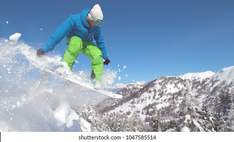 CLOSE UP: Professional snowboarder rides down a perfect snowy hill and jumps high in the air. Extreme rider on snowboard jumps off a snow covered ledge on a beautiful winter day in glorious mountains.