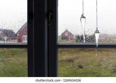 Close up: Rain drops as window decoration on the right side (selected focus) in front of a window on a rainy day, blurred thatched houses in the background, Denmark