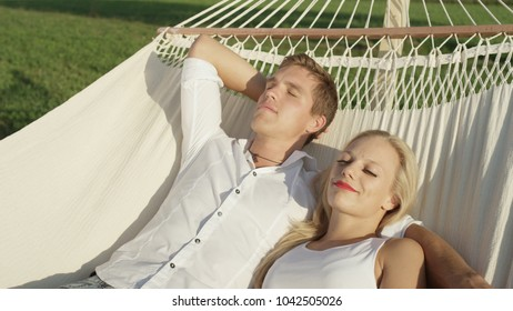 CLOSE UP: Romantic young Caucasian couple sleeping in embrace in swaying hammock. Lovely girl and boy on lovely date in sunny nature lounging on swinging sling in the tranquil spring countryside.