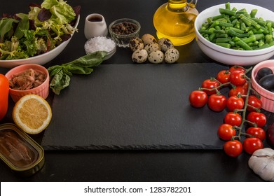 Close up. Rustic still life. French food.  Ingredients for making French traditional niçoise (nicoise) salad. Black background. Copy space.