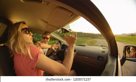 CLOSE UP: Side view of young couple dancing in their car while they drive through the idyllic sunny countryside. Carefree Caucasian couple enjoying their scenic road trip on a beautiful summer evening