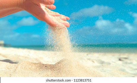 CLOSE UP: Small grains of white sand sift through unrecognizable young woman's fingers. Gentle summer breeze blows away coarse sand in playful female's hand. Girl holds up a handful of white sand.