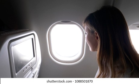 CLOSE UP: Smiling businesswoman looking through the window of a transatlantic passenger jet plane. Female traveler enjoying the breathtaking view of space and clouds from her comfortable window seat.