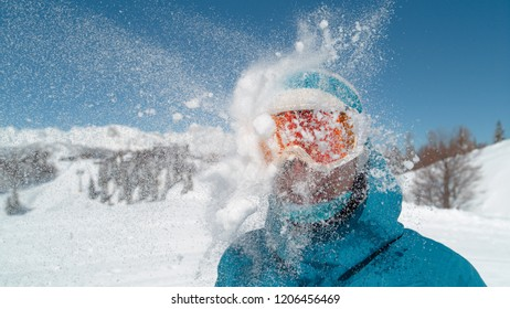 CLOSE UP: Smiling girl wearing ski goggles gets hit in the head by a big snowball. Excited young female tourist gets struck in the head by a flying snowball during a snowfight in the sunny nature.