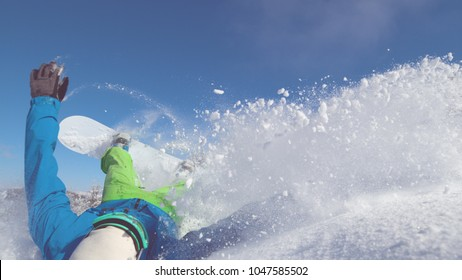 CLOSE UP: Snowboarder speeding down dangerous mountain falls into deep snow. Cross country rider crashes while carving down snowy mountain and leaves a trail of snowflakes behind him. Adrenaline sport