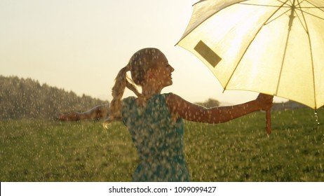 CLOSE UP: Spectacular golden sun beams shine on carefree young woman dancing in rain. Easygoing blonde girl lets the refreshing summer rain fall down on her while she twirls alone in the green meadow.