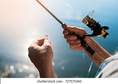 Close up. Spinning with the fishing reel in the right hand, fishing hook on the line with the bait in the left hand against the background of the water, in which the sun is reflected