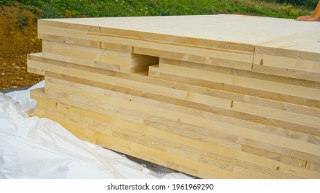 CLOSE UP: A stack of CLT wall panels lie uncovered at a construction site of a modern housing project made of a sustainable materials. Wind blows white tarp off the glued-laminated timber wall boards.