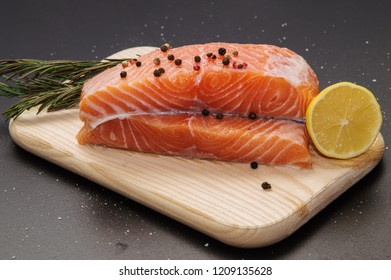 Close up, still life. Ingredients. Fresh orange salmon steak surrounded by lemon, spices and herbs on a wooden board. Black background.