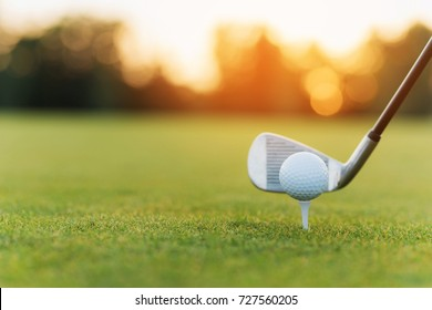 Close up. Stylish metal golf club and golf ball on a stand, against a sunset background. Low angle