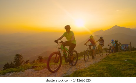CLOSE UP, SUN FLARE: Group of active friends enjoying a scenic cross country bicycle ride at sunset. Young travelers riding their mountain and electric bikes along a narrow trail at golden sunrise.