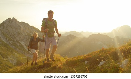 CLOSE UP, SUN FLARE: Happy tourists hiking in the stunning mountains of Slovenia on a sunny summer day. Athletic couple trekking in the Julian Alps at sunrise. Man and woman exploring golden landscape