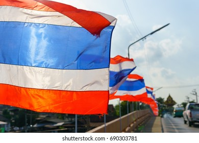 close up. thai flags on the pole blown by wind at the bridge in sunny day