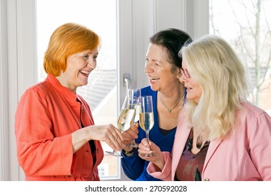 Close up. Three Happy Adult Women Friends in Trendy Attire Tossing Glasses of White Wine While Laughing at Something.