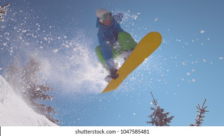 CLOSE UP: Thrilled snowboarder riding off piste in ski resort does an awesome trick in air on perfect winter day. Male rider enjoys epic adrenaline filled day on the freshly covered mountain slopes.