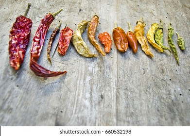 Close up, top shot of various colorful, different color dried chili peppers, paprika collection on rustic wooden table, red, orange, green, yellow, space for text, selective focus, palette of colors