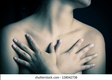 close up, topless woman body covering her breast with hand, color processed