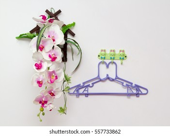 Close up, Two hanger on white wall near fake orchid.