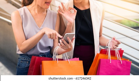 close up, two young happy women talking shopping, sale, consumerism and people concept. fashion tone.