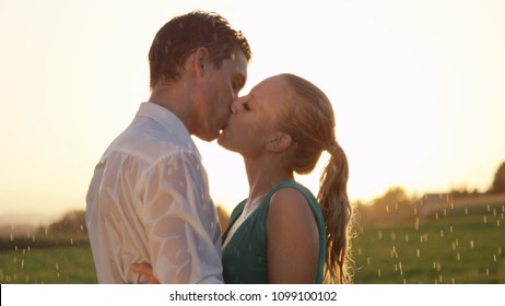 CLOSE UP: Two young lovers kiss in the rain while they dance in the countryside at picturesque summer sunset. Boyfriend and girlfriend kiss during their romantic date on a breathtaking spring morning.