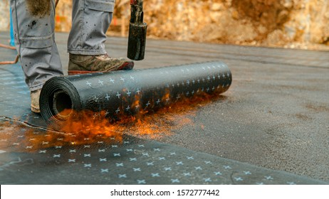 CLOSE UP: Unrecognizable laborer melts a roll of tar onto the foundation of a house under construction. Hard-working male contractor waterproofing a developing building. Man melting a bitumen roll.