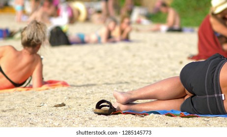 close up. unrecognizable people resting on the beach, with a lot of unrecognizable people sunbathing in the background
