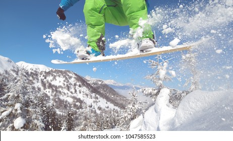 CLOSE UP: Unrecognizable snowboarder jumping in the air leaves a cool trail of fresh snow behind him. Extreme professional cross country snowboarder riding off piste jumps in the sky off powder snow.