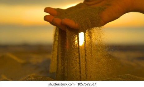 CLOSE UP: Unrecognizable woman grabs a handful of dry sand and lets it fall between her fingers. Young female traveler on a sunny beach in Fiji sifts coarse beach sand between her gentle fingertips.