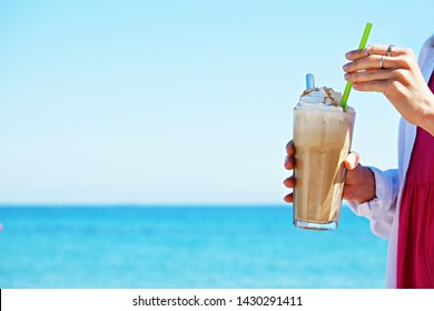 Close up, unrecognizable young woman holding glass of iced coffee at the beach, blue clear water. Attractive female, greek frappe drink in hands, enjoying sea shore view. Copy space, background