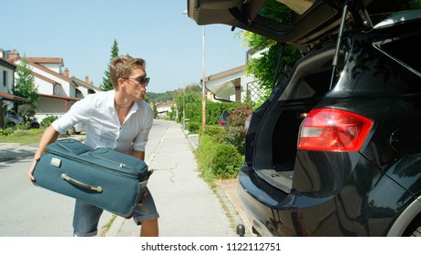 CLOSE UP: Whistling young male tourist throwing his bags into big black SUV before driving away from home to go on awesome road trip. Carefree Caucasian man packing for summer holiday with friends.