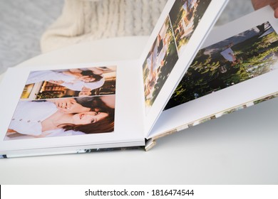 close up. a woman flips through a photo book from a family pregnancy photo shoot. beautiful and convenient storage of photos. memory of an important period.