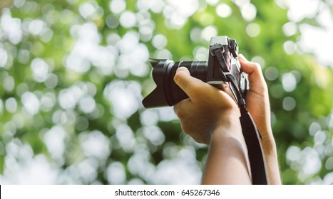 Close up, Yong man asian photographer holding digital camera mirrorless with lens equipment for take a photo and picture memories travel landscape trip lifestyle.
