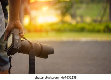 Close up, Yong man asian photographer holding digital camera DSLR with lens telephoto equipment for take a photo and picture memories travel landscape trip lifestyle.
