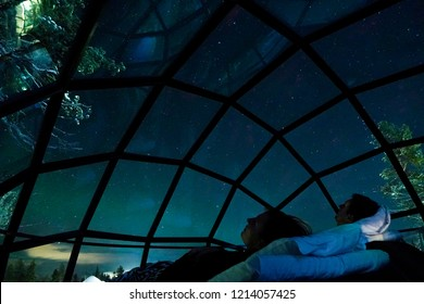 CLOSE UP: Young boyfriend and girlfriend enjoying a romantic evening under the stars and colorful sky. Tourist couple lying in the comfortable bed and waiting for the breathtaking northern lights.